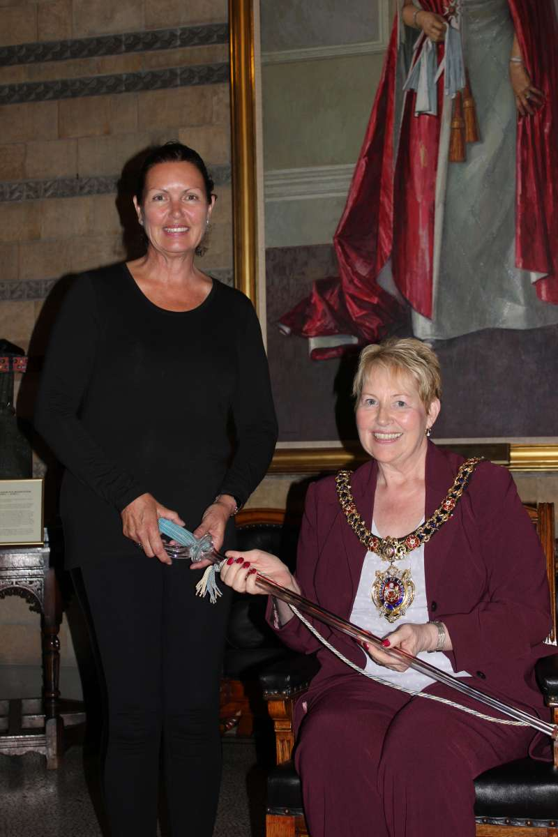 Janette Cox presents the Lord Mayor with a glass sword used at the opening of Manchester Town Hall in 1877