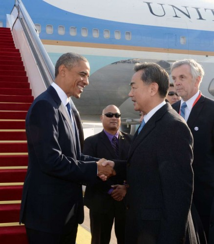 U.S. President Barack Obama  is welcomed by Chinese Foreign Minister Wang Yi upon his arrival in Beijing, China, Nov. 10, 2014. Obama is in Beijing to attend the 22nd Asia-Pacific Economic Cooperation (APEC) Economic Leaders' Meeting and pay a state visit to China.