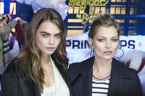 British models Cara Delevingne (L) and Kate Moss pose for photos to unveil the Printemps Christmas vitrine in Paris, France,