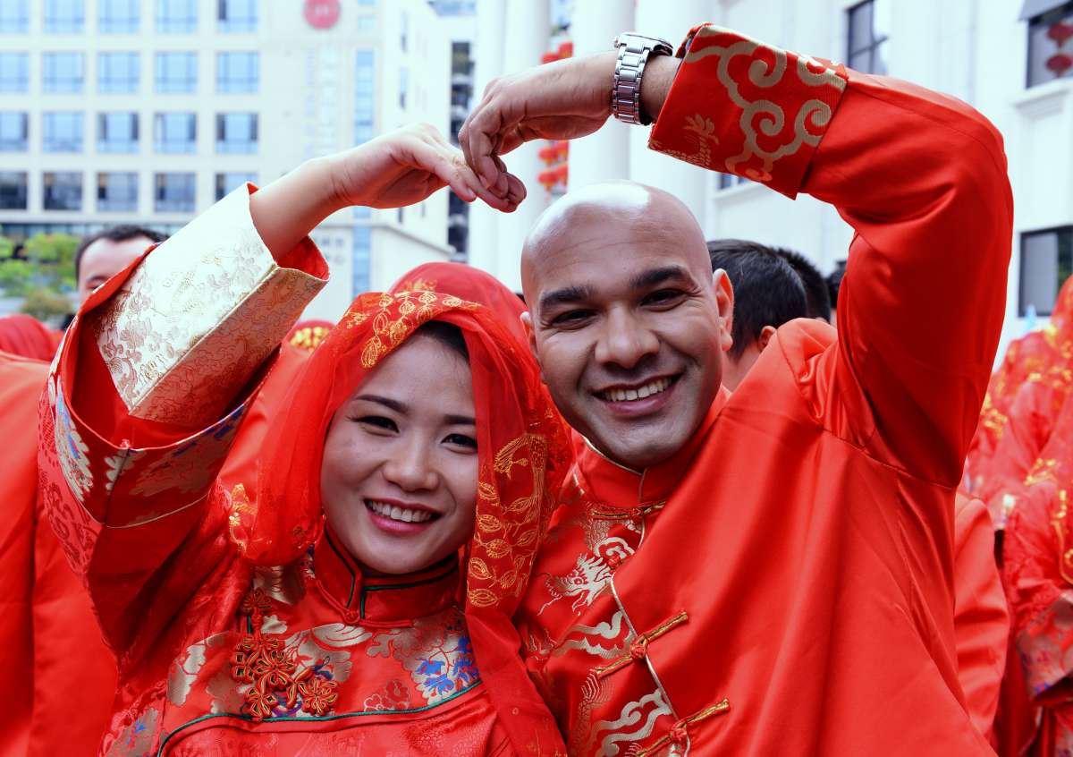 A new couple pose for photos during a group wedding ceremony in Fuzhou, capital of southeast China's Fujian Province, Nov. 3, 2014. A group wedding ceremony was held here Monday.