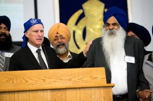 California Governor Jerry Brown holds a kirpan, a ceremonial sword carried by baptized Sikhs, given to him by Didar S. Bains, right center, during a ceremony Sunday honoring Bains at the Sikh temple in West Sacramento. Photo Credit: The Sacramento Bee