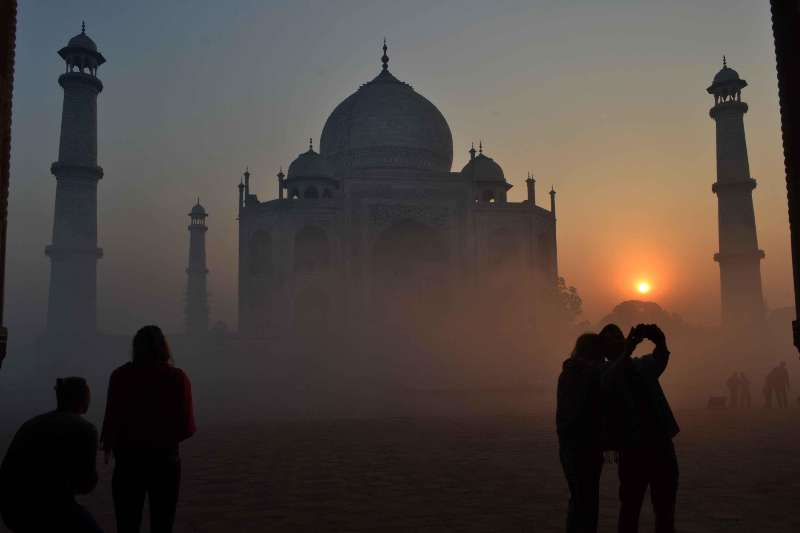 A spectacular view of Taj Mahal with a thin blanket of fog around it during the sunrise in Agra.