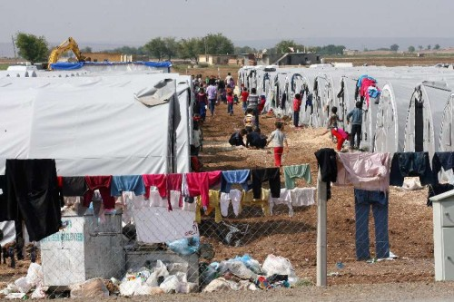 Syrian Kurdish refugees are seen the Turkish-Syrian border in Sanliurfa province, Turkey, Oct. 17, 2014. About 180,000 Syrian Kurds fled into southeastern Turkey in the past four weeks, away from violence of Islamic State (IS) militants who seized dozens of Kurdish villages in northern Syria.