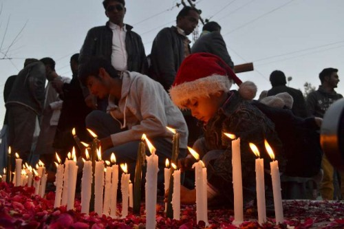 Pakistani Christians light candles to pay their respect to victims of the militant attack on an army-run school, in southwest Pakistan's Quetta, Dec. 19, 2014. At least 141 people, mostly children, were killed by Taliban terrorists who attacked the army-run school in Pakistan's northwestern provincial capital of Peshawar on Dec. 16.