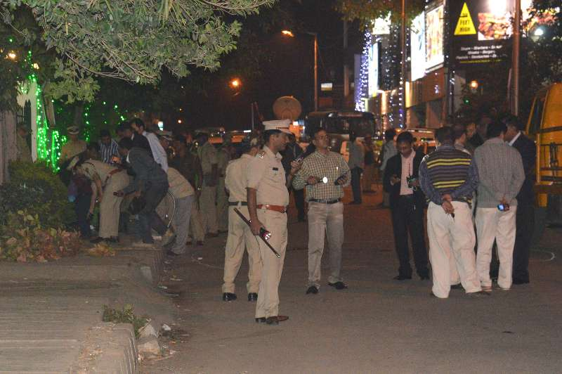 Bengaluru: Policemen the site of the low intensity bomb blast that rocked Church Street area of Bengaluru on Dec 28, 2014. Two people, including a woman, were injured in the blast near a food outlet in the city centre. (Photo: IANS)