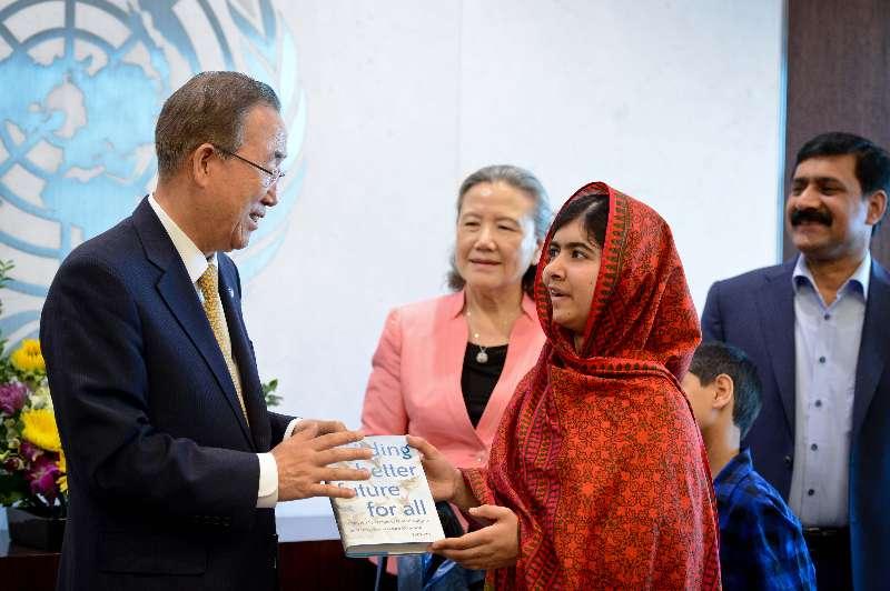 UN Secretary-General Ban Ki-moon (L, front) gives a book as a gift to Malala Yousafzai
