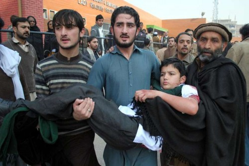 Volunteers hold an injured boy at a hospital in northwest Pakistan's Peshawar, Dec. 16, 2014. At least 84 people including 81 students had been killed and 83 others injured as a group of militants launched an attack on an army-run public school in Peshawar of Pakistan's northwest Khyber Pakhtunkhwa province on Tuesday morning, chief minister of the province said.