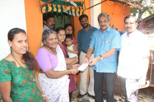 Union Defence Minister Manohar Parrikar hands over BJP membership card to a family in Ribandar, Goa.FILE PHOTO
