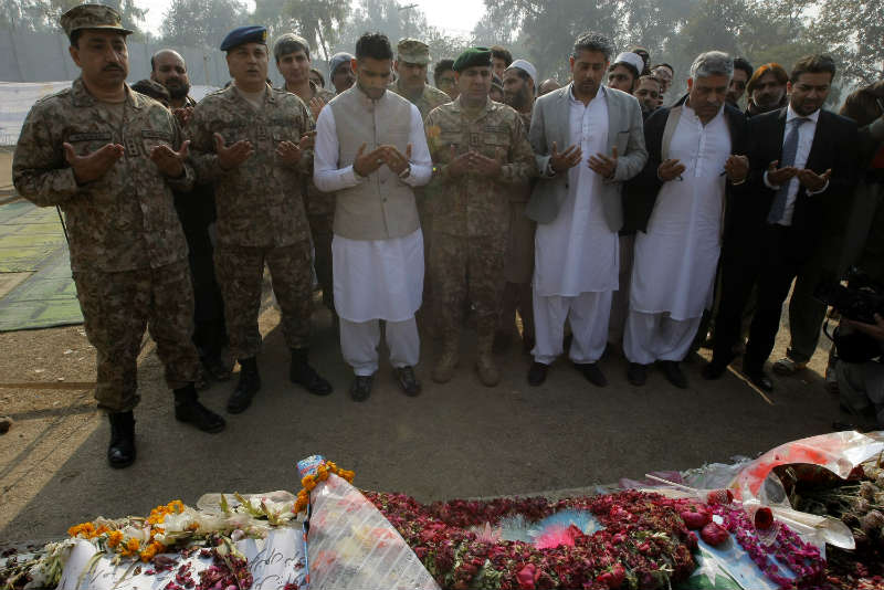 British boxer Amir Khan (3rd L, front) prays with Pakistani military officials at a memorial in the army-run school where 150 people were massacred by the Taliban in northwest Pakistan's Peshawar.