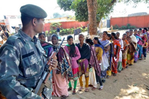 A soldier stands guard at a polling booth as women queue-up to cast their votes during the third phase of Jharkhand assembly polls in Maoist infested Rampur village, near Khijri on Dec 9, 2014.