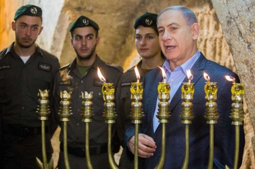 Israeli Prime Minister Benjamin Netanyahu attends a ceremony to mark the fifth night of Hanukkah at the Western Wall in the Old City of Jerusalem, on Dec. 20, 2014. Hanukkah, also known as the Festival of Lights and Feast of Dedication, is an eight-day Jewish holiday commemorating the rededication of the Holy Temple