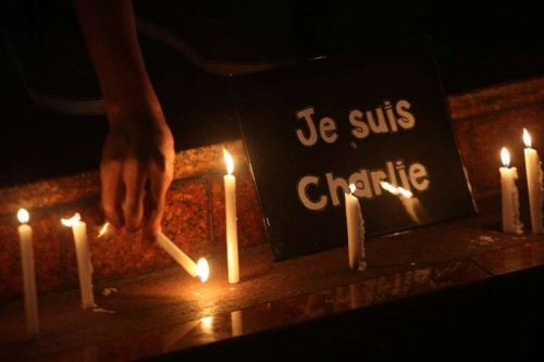 "A member of the National Union of Journalists of the Philippines (NUJP) lights candles in front of a placard that reads ""je suis Charlie"" (I am Charlie) during a candle lighting ceremony in Quezon City, the Philippines, Jan. 9, 2015. The NUJP denounced the attack on French satirical magazine Charlie Hebdo which killed 12 people and wounded 11 others."