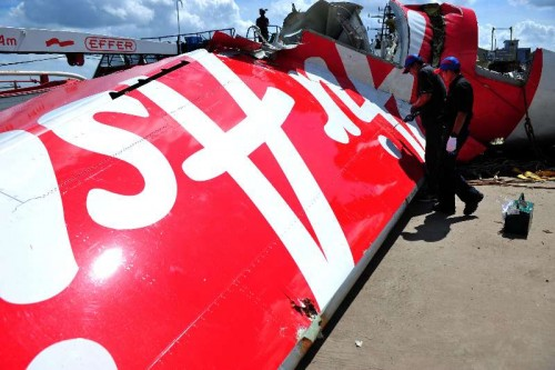 Members of Indonesia's National Transportation Safety Committee work on the tail of AirAsia Flight QZ8501 at Kumai port, Pangkalan Bun, Central Borneo, Indonesia, Jan. 12, 2015. After days of search, Indonesian navy divers have finally succeeded in retrieving the flight data recorder (FDR) of the crashed AirAsia Flight QZ8501 in the Java Sea, shedding light on determining the cause of the fatal crash with 162 people onboard.
