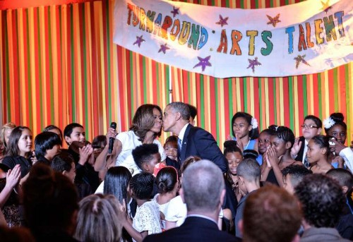 U.S. President Barack Obama and first lady Michelle Obama kiss at the Turnaround Arts Talent Show hosted by Michelle Obama and the President's Committee on the Arts and the Humanities (PCAH) at the White House in Washington D.C., capital of the United States, May 20, 2014. Turnaround Arts is a program to help turn around low-performing schools and increase student achievement through arts education.