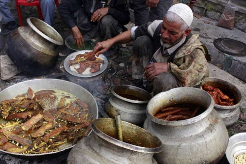 Kashmir: People busy cooking Wazwan - a Kashmiri cuisine that consists of thirty-six courses in Kashmir valley. The cuisine comprises of Maithi maaz, Rista (meatballs), Lahabi Kabab or Moachi Kabab (flattened mutton kababs cooked in yogurt), Waza Kokur (two halves or two full chicken cooked whole), Daeni Phoul ( a mutton dish), Doudha Ras (mutton cooked in sweet milk gravy), Rogan Josh (tender lamb cooked with Kashmiri spices),Tabak Maaz (ribs of lamb simmered in yogurt), Daniwal Korma (a mutton curry with coriander), Waza Palak (green spinach cooked with small pounced mutton balls known as Paliki Riste), Aab Gosh (lamb cooked in milk curry), Marchwangan Korma (an extremely spicy lamb preparation), Kabab, Gushtaba (meatballs in white yogurt gravy), Yakh'n (delicately spiced yogurt curry), Ruwangan Chhaman (cheese squares with Tomato gravy), Dum Aelva (potatoes cooked in yogurt gravy), Muji Chetintin (a radish and walnut chutney), Phirni (a milk pudding thickened with semolina or ground rice). (Photo: IANS)