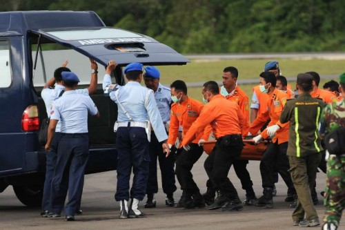 Search and Rescue (SAR) people carry the body bag containing the eighth victim of AirAsia flight QZ8501 to ambulance at Iskandar Air Base in Pangkalan Bun, Central Kalimantan, Indonesia, Jan. 1, 2015.