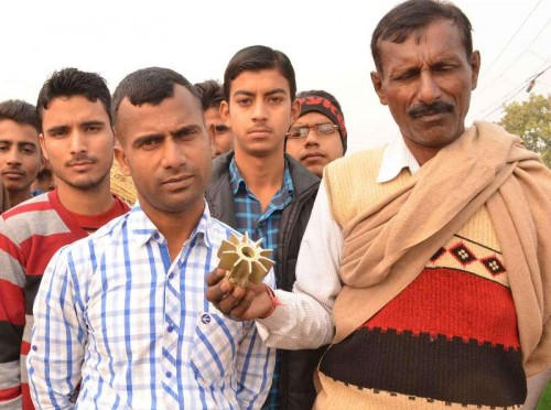 Villagers show a portion of a mortar allegedly fired from Pakistan at Keso-Kamoor village in Samba district of Jammu and Kashmir on Jan 5, 2015.