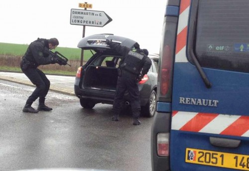 Policemen check a car in Dammartin-en-Goele, northeast of Paris, where two brothers suspected of Charlie Hebdo attack held one person hostage as police cornered the gunmen, on Jan. 9, 2015. The Kouachi brothers, suspects of Charlie Hebdo attacks, were killed during French security force's assault on Friday evening, and the hostages are alive.