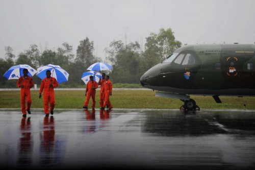 Indonesian air force pilots hold umbrellas during heavy rain while their plane is canceled to fly at Pangkalan Bun, Indonesia, Jan. 4, 2015. The search and rescue team has yet to find the black boxes of crashed AirAsia flight QZ8501 as bad weather still lingers in the crash site, an Indonesian official said