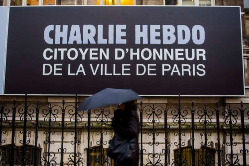 """A pedestrian walks past an advertisement of Charlie Hebdo in Paris, France, on Jan. 9, 2015. Paris on Friday made the satirical magazine Charlie Hebdo an """"honorary citizen"""" as part of support to the weekly which lost its main cartoonists in a deadly shooting on Wednesday."""