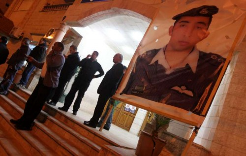 People stand by a poster of the Jordanian pilot Moaz al-Kasasbeh after the release of a video purportedly showing Islamic State captive Jordanian pilot being burnt alive in the pilot's hometown Karak, Jordan, on Feb. 3, 2015. Jordanian government on Tuesday confirmed the killing of Jordanian pilot held captive by the Islamic State (IS),