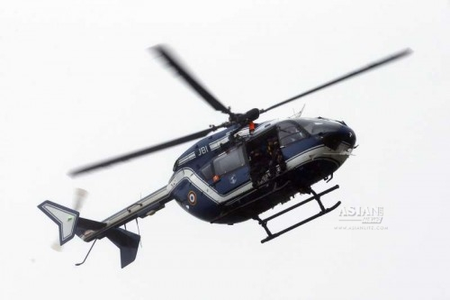 A French police helicopter flies over the city of Paris.