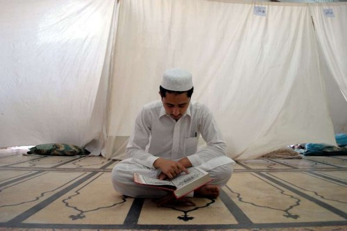 A Pakistani Muslim reads holy Koran during Itikaf at a mosque during Ramadan in northwest Pakistan's Peshawar on July 19, 2014. Itikaf is a spiritual retreat in a mosque, and is usually held during the last 10 days of Ramadan, during which Muslims will spend the evening and night in the mosque, devoting their time to solitary prayers and reading the Koran.