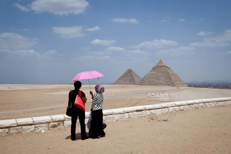 Tourists look at the Pyramids of Giza, Cairo, Egypt