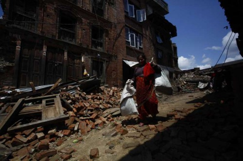 A woman collects her belongings from houses damaged by earthquake in Bhaktapur, Nepal, April 27, 2015. Death toll climbed to 3,815 following a massive 7.9-magnitude earthquake in Nepal Saturday, while 7,046 sustained injuries, says the country's ministry of foreign affairs