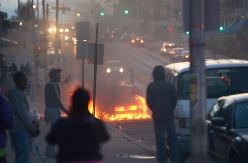 A car burns in Baltimore, Maryland, the United States, April 27, 2015. Maryland governor Larry Hogan Monday evening declared a state of emergency and activated the National Guard to address the escalating violence and unrest in Baltimore City following the funeral of a 25-year-old black man who died after he was injured in police custody.
