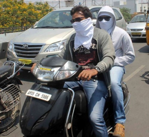 People cover their face to protect themself from the heat wave in Hyderabad