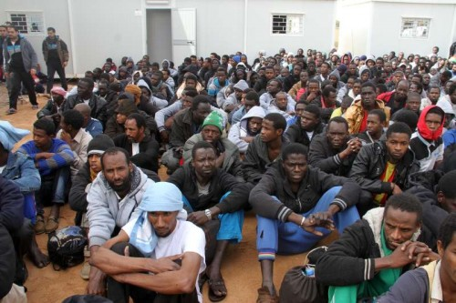 Dozens of illegal immigrants gather in a yard guarded by Libyan police in Misrata, Libya, on Feb. 18, 2015. Libya has long been a transit point for migrants seeking to reach Malta, Italy, and other places in Europe