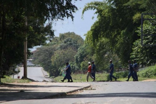 Burundian police walk towards the airport in Bujumbura, capital of Burundi, May 14, 2015. At least 15 workers including journalists and other agents Thursday got stranded inside Burundi National Radio and Television (RTNB) in an attack by pro-coup forces,