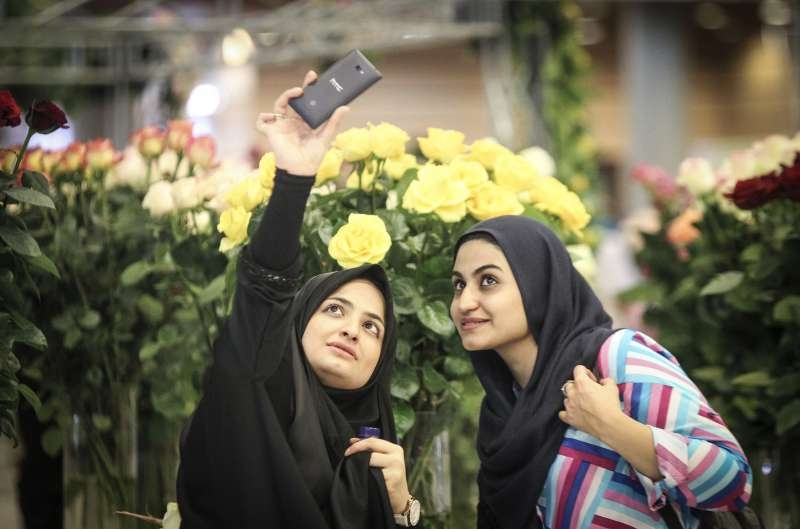 Women takes a selfie as they visit the 13th International Flower Exhibition in Tehran, capital of Iran (File)