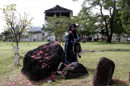 An Indonesian Muslim woman sow flowers during the commemoration of 10th anniversary of the devastating tsunami at Ulee Lheue mass grave in Banda Aceh, Indonesia, Dec. 26, 2014. A ceremony marking the devastating tsunami that hit Indonesia the worst ten years ago was held here on Friday, featuring appreciation to donor countries participating in rebuilding and rehabilitating Aceh to what it is today.