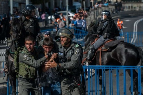"A Palestinian demonstrator is detained by Israeli policeman near Damascus Gate in the Old City of Jerusalem, on May 17, 2015. Tens of thousands of Jews marched Sunday through east Jerusalem's Muslim Quarter, sparking scuffles between Palestinians and the police. The controversial march celebrated Israel's 48th Jerusalem Day, marking the ""reunification"" of the city after Israel seized the Arab eastern part of the city during the 1967 Mideast War"