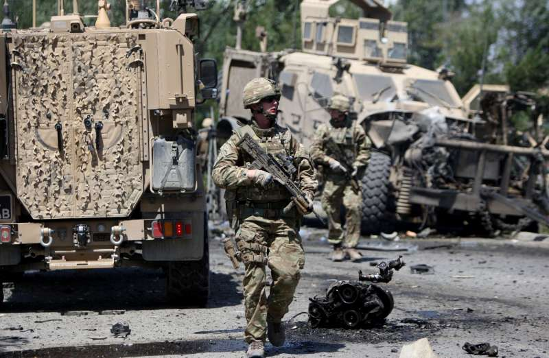 Foreign soldiers walk around a destroyed military vehicle following a suicide car bombing in Kabul, Afghanistan, June 30, 2015. Several civilians were killed and wounded Tuesday after a suicide car bombing targeted a foreign military convoy near airport in Afghan capital of Kabul.