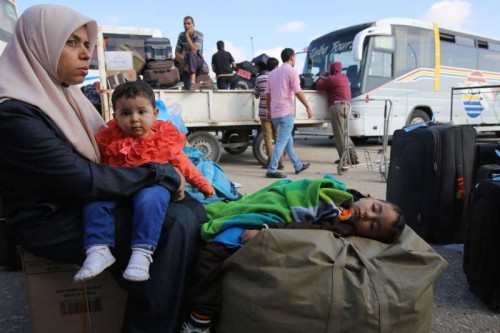 A Palestinian woman holds her boy as she waits for a travel permit to cross into Egypt, at the Rafah border crossing between Egypt and the southern Gaza Strip, June 13, 2015. Egyptian authorities opened the Rafah border crossing on Saturday for three days, in both directions to allow entry and exit of Gazan patients and students, for the first time since March 11, Palestinian officials said.