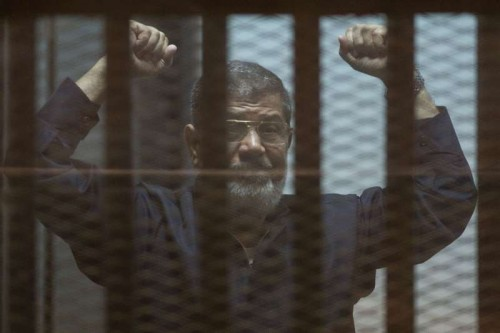 Egypt's ousted President Mohamed Morsi gestures behind the defendants' cage at a court in Cairo, Egypt, on June 16, 2015. An Egyptian court on Tuesday confirmed the death sentence against ousted President Mohamed Morsi over mass jailbreak during the 2011 political turmoil, state-run Nile TV reported.