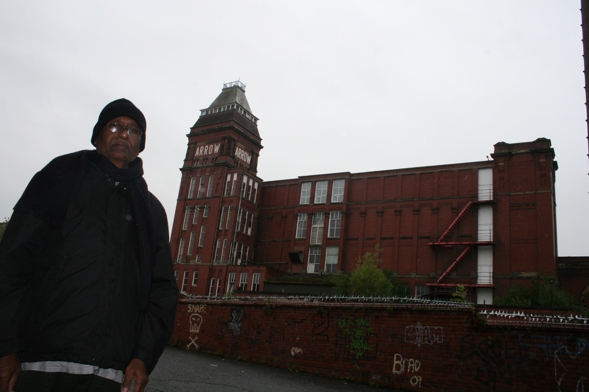 A former employee stands besides his old working place in Rochdale