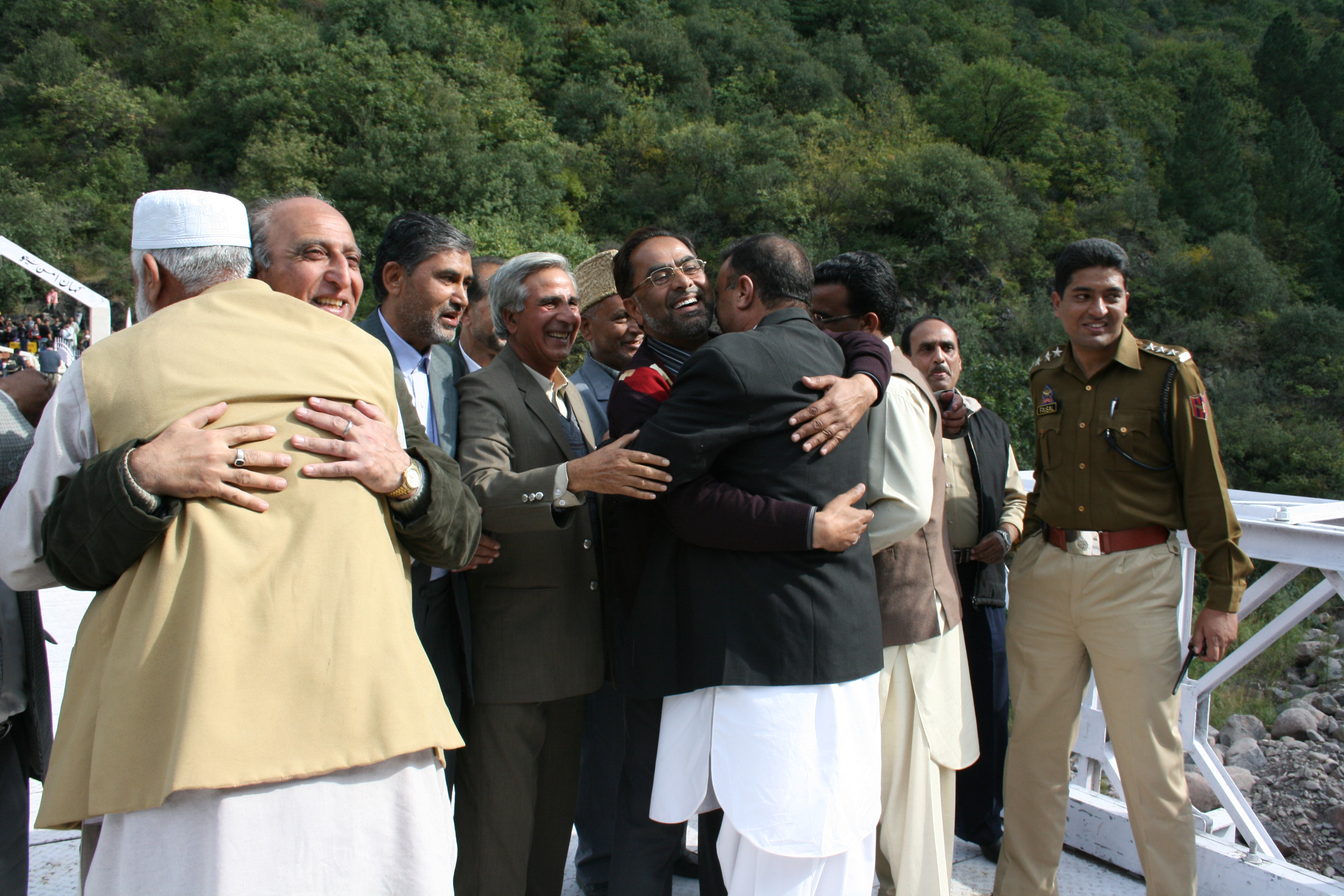 Political leaders and traders from Azad Jammu and Kashmir (Pakistani side and Jammu and Kashmir (Indian side) hug on the Chakoti Bridge after 60 years of separation