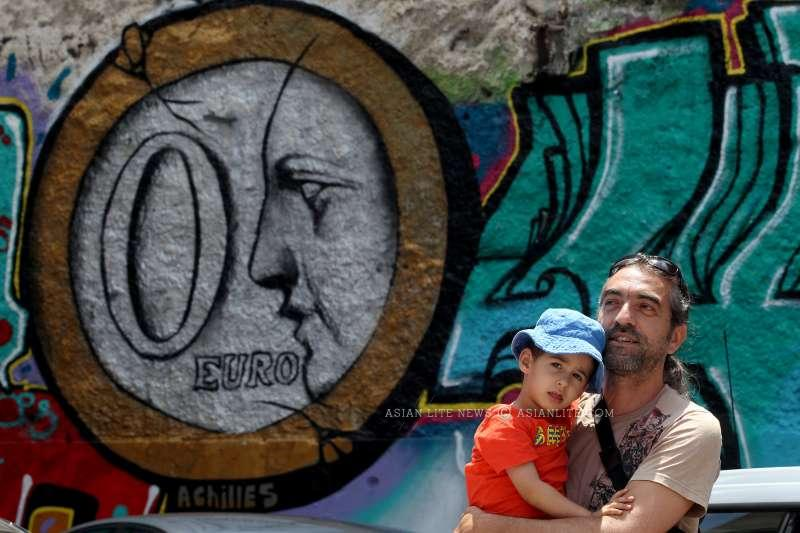 A man and a baby stand before a graffiti on a wall in central Athens, Greece