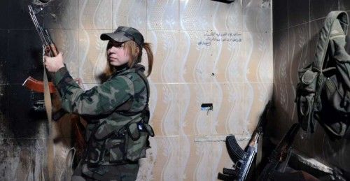 A female sniper takes positon in a buliding in Daraya suburb of the capital Damascus, Syria