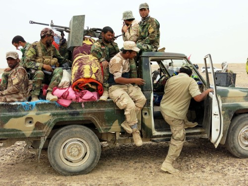Fighters of Hashid al-Shaabi forces get on a truck at the frontline against Islamic State (IS) militants in the Tharthar lake area, northeast of Fallujah, some 50 km west of Baghdad, on June 01, 2015.