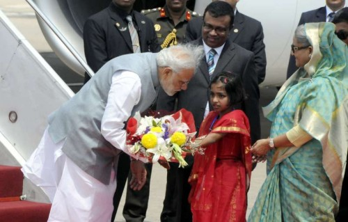 Indian Prime Minister Narendra Modi (L, front) receives a bunch of flowers from a Bangladeshi girl after arriving at the Hazrat Shahjalal International Airport in Dhaka, Bangladesh, June 6, 2015. Indian Prime Minister Narendra Modi arrived in Dhaka on Saturday for a two-day visit to Bangladesh. Prime Minister Sheikh Hasina greeted her counterpart at the Hazrat Shahjalal International Airport with a 19-gun salute.