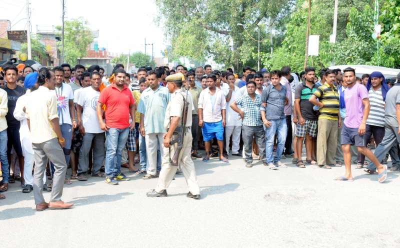 People gather near the Dinanagar police station, where the heavily-armed terrorists are holed up, on July 27, 2015. At least five people were killed and 10 injured when heavily-armed terrorists wearing army fatigues hijacked a car, drove down to Dinanagar in Punjab's Gurdaspur district, peppered the bus stand with bullets and then stormed a police station -- shattering two decades of calm in the state.