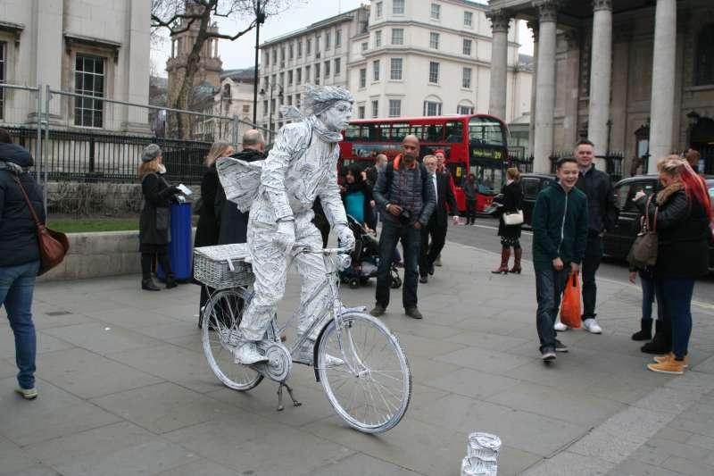A man entertains visitors at Trafalgar Square in London