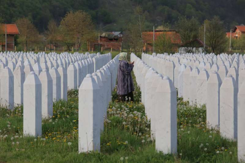 A mother prays for her son at the massacre site Serbrenica