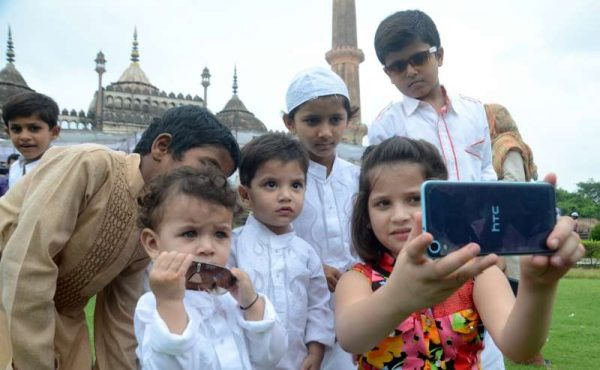 A girl takes a selfie with her friends on the occasion of Eid-ul-Fitr at Bara Imambara in Lucknow on July 18, 2015
