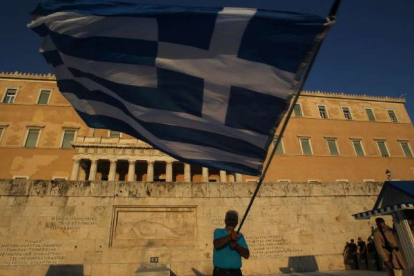 A protester holds a Greek flag during a Pro-Euro rally in front of the parliament building in Athens, Greece, on July 9, 2015. Greece's pro euro protesters returned to the streets Thursday evening, as the government approved the debt deal proposal which will be sent in coming hours to the country's lenders to stave off a looming bankruptcy and Grexit.